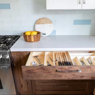 Foto på ett mellanstort maritimt vit kök, med en rustik diskho, luckor med infälld panel, skåp i slitet trä, bänkskiva i kvarts, blått stänkskydd, stänkskydd i glaskakel, rostfria vitvaror, mellanmörkt trägolv, en köksö och gult golv