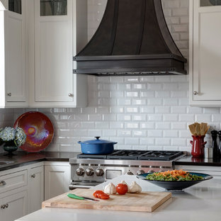 This is an example of a medium sized traditional u-shaped kitchen/diner in Chicago with a submerged sink, beaded cabinets, white cabinets, granite worktops, white splashback, metro tiled splashback, stainless steel appliances, medium hardwood flooring and an island.