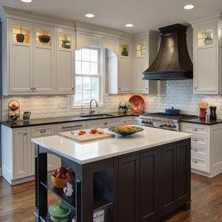 Klassisk inredning av ett mellanstort flerfärgad flerfärgat l-kök, med en undermonterad diskho, luckor med profilerade fronter, vita skåp, granitbänkskiva, vitt stänkskydd, stänkskydd i tunnelbanekakel, rostfria vitvaror, mörkt trägolv och en köksö