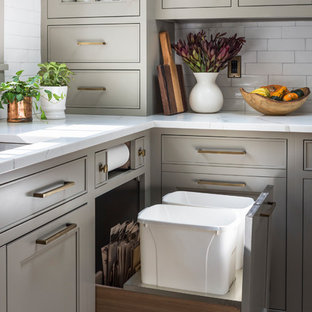 ニューヨークの大きいカントリー風おしゃれなキッチン (ダブルシンク、シェーカースタイル扉のキャビネット、ベージュのキャビネット、クオーツストーンカウンター、白いキッチンパネル、セラミックタイルのキッチンパネル、黒い調理設備、無垢フローリング、茶色い床、白いキッチンカウンター) の写真