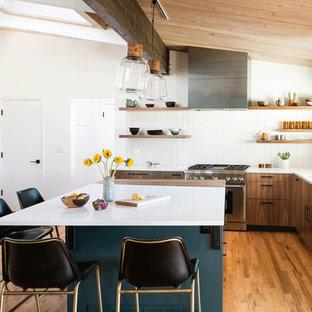 Inspiration för ett retro vit vitt l-kök, med en undermonterad diskho, släta luckor, skåp i mellenmörkt trä, vitt stänkskydd, stänkskydd i mosaik, rostfria vitvaror, mellanmörkt trägolv, en köksö och brunt golv