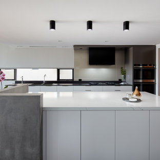 Photo of a contemporary galley eat-in kitchen in Sydney with a drop-in sink, flat-panel cabinets, white cabinets, grey splashback, glass sheet splashback, black appliances, with island, grey floor and white benchtop.