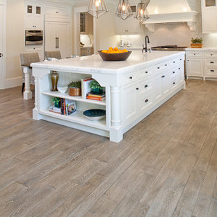 Kitchen - large traditional l-shaped light wood floor kitchen idea in Orange County with an island, shaker cabinets, white cabinets, marble countertops, white backsplash and stainless steel appliances