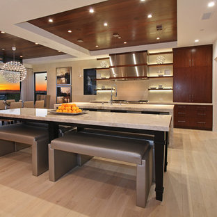 Large contemporary l-shaped eat-in kitchen in Orange County with flat-panel cabinets, dark wood cabinets, limestone benchtops, with island, an undermount sink, beige splashback, stainless steel appliances, light hardwood floors, ceramic splashback and brown floor.