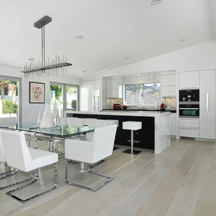 Inspiration for a large contemporary galley light wood floor and brown floor eat-in kitchen remodel in Orange County with an undermount sink, flat-panel cabinets, white cabinets, marble countertops, white backsplash, stainless steel appliances, an island and marble backsplash