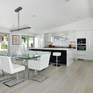 Immagine di una grande cucina design con lavello sottopiano, ante lisce, ante bianche, top in marmo, paraspruzzi bianco, elettrodomestici in acciaio inossidabile, parquet chiaro, isola, paraspruzzi in marmo e pavimento marrone