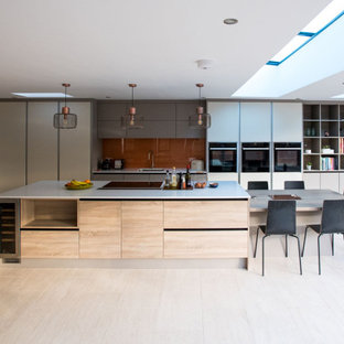 This is an example of an expansive contemporary galley kitchen in Hampshire with a submerged sink, flat-panel cabinets, grey cabinets, brown splashback, glass sheet splashback, integrated appliances, an island, beige floors and white worktops.