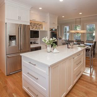 Immagine di una cucina chic di medie dimensioni con lavello stile country, ante con bugna sagomata, ante bianche, top in quarzo composito, paraspruzzi grigio, paraspruzzi con piastrelle di vetro, elettrodomestici in acciaio inossidabile e pavimento in legno massello medio