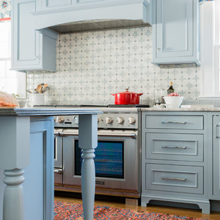 Traditional kitchen ideas - Example of a classic l-shaped medium tone wood floor and brown floor kitchen design in Boston with an undermount sink, recessed-panel cabinets, blue cabinets, multicolored backsplash, stainless steel appliances and an island