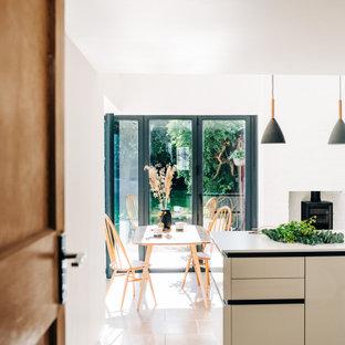 カーディフのコンテンポラリースタイルのおしゃれなキッチン (ドロップインシンク、フラットパネル扉のキャビネット、ベージュのキャビネット、クオーツストーンカウンター、レンガのキッチンパネル、パネルと同色の調理設備、ライムストーンの床、アイランドなし、ベージュの床、白いキッチンカウンター) の写真