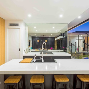 Inspiration for a contemporary galley open plan kitchen in Gold Coast - Tweed with a drop-in sink, flat-panel cabinets, metallic splashback, mirror splashback, black appliances, concrete floors, with island, grey floor, light wood cabinets, granite benchtops and white benchtop.