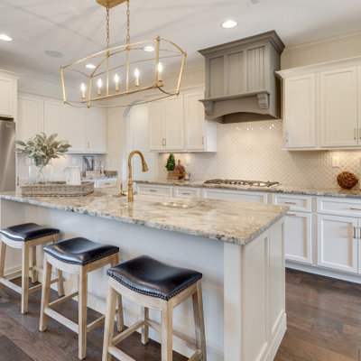 Large elegant l-shaped dark wood floor and brown floor open concept kitchen photo in Other with an island, a farmhouse sink, shaker cabinets, white cabinets, white backsplash, mosaic tile backsplash, stainless steel appliances and gray countertops