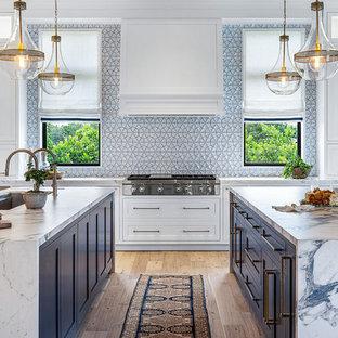 Inredning av ett maritimt flerfärgad flerfärgat kök, med en undermonterad diskho, skåp i shakerstil, vita skåp, flerfärgad stänkskydd, rostfria vitvaror, ljust trägolv och flera köksöar