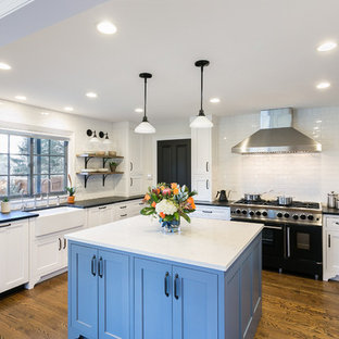 Design ideas for a large classic u-shaped kitchen/diner in Other with an island, a belfast sink, shaker cabinets, blue cabinets, granite worktops, white splashback, ceramic splashback, integrated appliances, dark hardwood flooring, brown floors and white worktops.