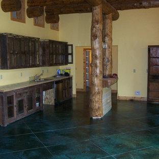 Cette photo montre une petite cuisine linéaire sud-ouest américain avec un évier posé, des portes de placard en bois vieilli, un électroménager en acier inoxydable et béton au sol.