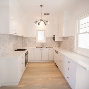 Photo of a nautical u-shaped enclosed kitchen in Adelaide with a double-bowl sink, flat-panel cabinets, white cabinets, laminate countertops, grey splashback, white appliances, plywood flooring, no island and beige floors.