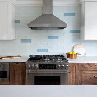 Idéer för ett mellanstort maritimt vit kök, med en rustik diskho, luckor med infälld panel, skåp i slitet trä, bänkskiva i kvarts, blått stänkskydd, stänkskydd i glaskakel, rostfria vitvaror, mellanmörkt trägolv, en köksö och gult golv