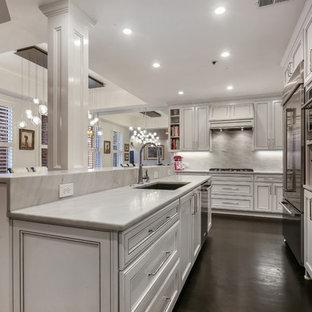 アトランタの中サイズのエクレクティックスタイルのおしゃれなキッチン (白いキャビネット、大理石カウンター、白いキッチンパネル、大理石の床、シルバーの調理設備の、濃色無垢フローリング、黒い床、白いキッチンカウンター、アンダーカウンターシンク、落し込みパネル扉のキャビネット) の写真