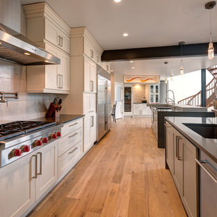 Traditional galley kitchen pantry in Denver with a double-bowl sink, shaker cabinets, white cabinets, engineered stone countertops, beige splashback, stone tiled splashback, stainless steel appliances, medium hardwood flooring, multiple islands and brown floors.