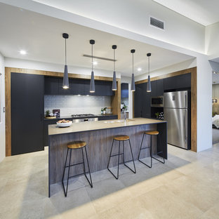 This is an example of a contemporary single-wall kitchen in Perth with an undermount sink, flat-panel cabinets, white splashback, subway tile splashback, stainless steel appliances, with island, beige floor, black benchtop, grey cabinets and quartz benchtops.