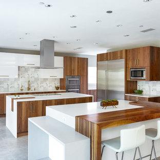 Inredning av ett modernt mycket stort vit vitt kök, med en enkel diskho, släta luckor, skåp i mellenmörkt trä, bänkskiva i kvarts, grått stänkskydd, stänkskydd i marmor, rostfria vitvaror, klinkergolv i porslin, flera köksöar och grått golv