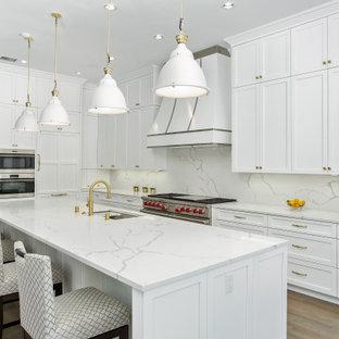 ダラスの広いトランジショナルスタイルのおしゃれなキッチン (アンダーカウンターシンク、落し込みパネル扉のキャビネット、白いキャビネット、クオーツストーンカウンター、白いキッチンパネル、クオーツストーンのキッチンパネル、シルバーの調理設備、濃色無垢フローリング、茶色い床、白いキッチンカウンター) の写真
