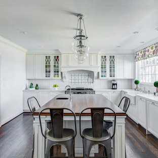 Large traditional kitchen designs - Inspiration for a large timeless l-shaped dark wood floor and brown floor kitchen remodel in Dallas with shaker cabinets, white cabinets, white backsplash and an island