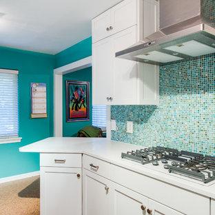 ダラスの小さいエクレクティックスタイルのおしゃれなキッチン (アンダーカウンターシンク、シェーカースタイル扉のキャビネット、白いキャビネット、クオーツストーンカウンター、マルチカラーのキッチンパネル、ガラス板のキッチンパネル、白い調理設備、コルクフローリング、茶色い床、白いキッチンカウンター) の写真