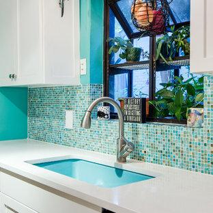 Exempel på ett avskilt, litet eklektiskt vit vitt parallellkök, med en undermonterad diskho, skåp i shakerstil, vita skåp, bänkskiva i kvarts, flerfärgad stänkskydd, glaspanel som stänkskydd, vita vitvaror, korkgolv, en halv köksö och brunt golv