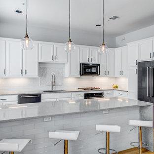 Inspiration för ett mellanstort vintage grå grått l-kök, med en undermonterad diskho, luckor med infälld panel, vita skåp, bänkskiva i kvarts, vitt stänkskydd, stänkskydd i glaskakel, svarta vitvaror, en halv köksö, mellanmörkt trägolv och brunt golv