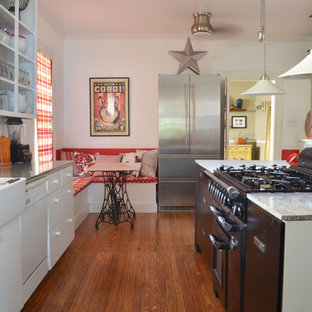 Traditional eat-in kitchen ideas - Eat-in kitchen - traditional eat-in kitchen idea in Dallas with a farmhouse sink, flat-panel cabinets, white cabinets and stainless steel appliances