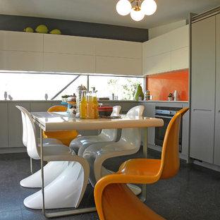 ダラスのミッドセンチュリースタイルのおしゃれなキッチン (フラットパネル扉のキャビネット、白いキャビネット、オレンジのキッチンパネル、ガラス板のキッチンパネル) の写真