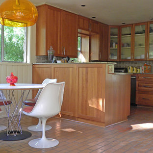Inspiration for a midcentury eat-in kitchen in Dallas with glass-front cabinets, medium wood cabinets, grey splashback, stainless steel appliances and brick floors.