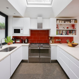 Inspiration for a medium sized contemporary u-shaped kitchen in London with a submerged sink, flat-panel cabinets, white cabinets, quartz worktops, red splashback, glass tiled splashback, stainless steel appliances, no island and marble flooring.