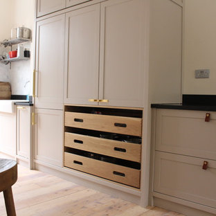 Large arts and crafts single-wall open plan kitchen in London with a farmhouse sink, shaker cabinets, medium wood cabinets, concrete benchtops, black splashback, slate splashback, panelled appliances, light hardwood floors, with island and multi-coloured floor.