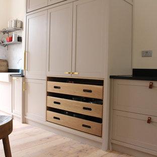 Idéer för stora amerikanska linjära kök med öppen planlösning, med en rustik diskho, skåp i shakerstil, skåp i mellenmörkt trä, bänkskiva i betong, svart stänkskydd, stänkskydd i skiffer, integrerade vitvaror, ljust trägolv, en köksö och flerfärgat golv