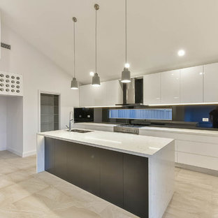 Design ideas for a large galley kitchen pantry in Sydney with a built-in sink, engineered stone countertops, black splashback, glass sheet splashback, stainless steel appliances, porcelain flooring, an island and multi-coloured floors.
