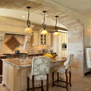 ロサンゼルスの地中海スタイルのおしゃれなキッチン (レイズドパネル扉のキャビネット、ベージュのキャビネット、ベージュキッチンパネル、ライムストーンの床) の写真