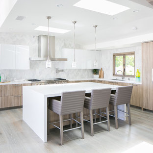 Contemporary kitchen designs - Inspiration for a contemporary l-shaped light wood floor and beige floor kitchen remodel in Orange County with flat-panel cabinets, light wood cabinets, stainless steel appliances, an island and white countertops