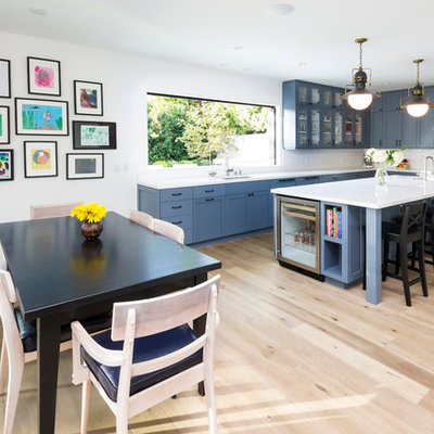 Example of a transitional l-shaped eat-in kitchen design in Los Angeles with an undermount sink, shaker cabinets, blue cabinets, white backsplash and stainless steel appliances