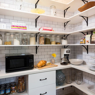 Transitional kitchen pantry photo in Los Angeles with white backsplash, subway tile backsplash and black appliances