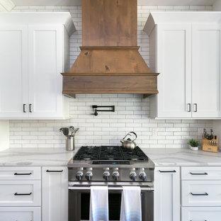 Foto på ett mycket stort lantligt vit kök med öppen planlösning, med en rustik diskho, skåp i shakerstil, vita skåp, bänkskiva i kvarts, vitt stänkskydd, stänkskydd i tegel, rostfria vitvaror och en köksö