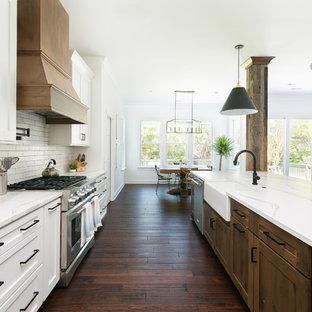 На фото: огромная параллельная кухня-гостиная в стиле кантри с раковиной в стиле кантри, фасадами в стиле шейкер, белыми фасадами, столешницей из кварцевого агломерата, белым фартуком, фартуком из кирпича, техникой из нержавеющей стали, островом, белой столешницей, темным паркетным полом и коричневым полом с