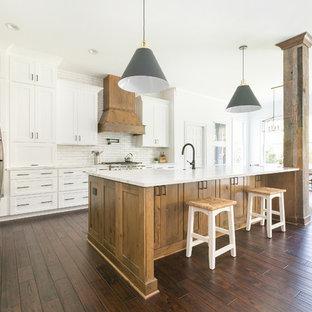 Bild på ett mycket stort lantligt vit vitt kök med öppen planlösning, med en rustik diskho, skåp i shakerstil, vita skåp, bänkskiva i kvarts, vitt stänkskydd, stänkskydd i tegel, rostfria vitvaror och en köksö