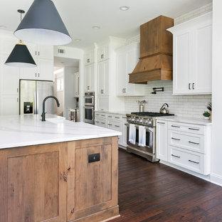 Пример оригинального дизайна: огромная кухня-гостиная в стиле кантри с раковиной в стиле кантри, фасадами в стиле шейкер, белыми фасадами, столешницей из кварцевого композита, белым фартуком, фартуком из кирпича, техникой из нержавеющей стали, островом и белой столешницей