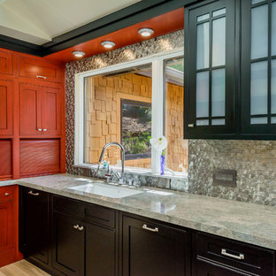 Inspiration for a mid-sized eclectic u-shaped eat-in kitchen in San Francisco with an undermount sink, beaded inset cabinets, black cabinets, granite benchtops, metallic splashback, metal splashback, stainless steel appliances, porcelain floors and with island.