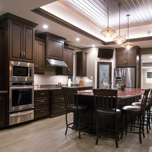 Large classic l-shaped kitchen/diner in Other with an integrated sink, raised-panel cabinets, dark wood cabinets, granite worktops, stainless steel appliances, vinyl flooring and an island.