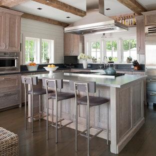 Inredning av ett maritimt stort l-kök, med rostfria vitvaror, bänkskiva i rostfritt stål, luckor med infälld panel, skåp i slitet trä, grått stänkskydd, mörkt trägolv och en köksö