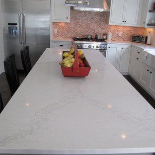 ニューヨークの広いカントリー風おしゃれなキッチン (エプロンフロントシンク、シェーカースタイル扉のキャビネット、白いキャビネット、クオーツストーンカウンター、赤いキッチンパネル、シルバーの調理設備、濃色無垢フローリング、セラミックタイルのキッチンパネル) の写真