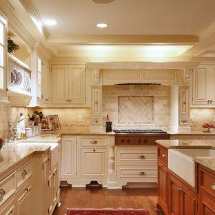 Large elegant u-shaped medium tone wood floor eat-in kitchen photo in New York with a farmhouse sink, raised-panel cabinets, beige cabinets, granite countertops, beige backsplash, stainless steel appliances, an island and travertine backsplash